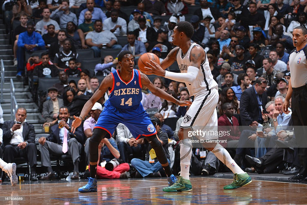 Justin Holiday #14 of the Philadelphia 76ers defends against <a gi-track='captionPersonalityLinkClicked' href=/galleries/search?phrase=MarShon+Brooks&family=editorial&specificpeople=4884862 ng-click='$event.stopPropagation()'>MarShon Brooks</a> #9 of the Brooklyn Nets on April 9, 2013 at the Barclays Center in Brooklyn, New York.