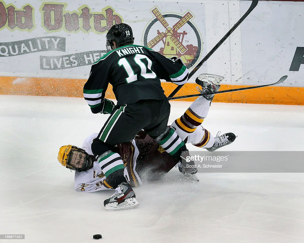 Justin Holl #12 of Minnesota gets knocked down by Corban Knight #10 of North Dakota January 19, 2013 at Mariucci Arena in Minneapolis, Minnesota.