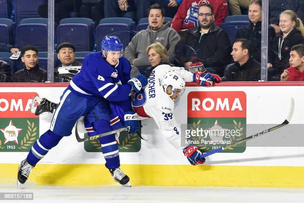 Justin Holl of the Toronto Marlies checks Jordan Boucher of the Laval Rocket during the AHL game at Place Bell on November 1 2017 in Laval Quebec...