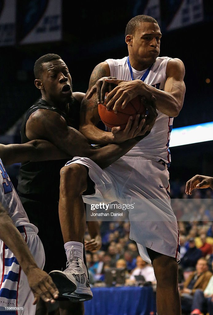 Justin Jackson #5 of the Cincinnati Bearcats and Cleveland Melvin #12 of the DePaul Blue Demons battle for the ball at Allstate Arena on January 15, 2013 in Rosemont, Illinois. Cincinnati defeated DePaul 75-70.