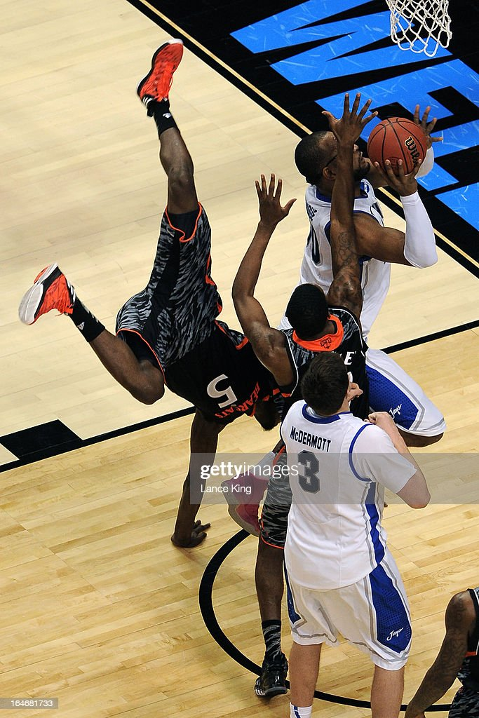 Justin Jackson #5 of the Cincinnati Bearcats falls while defending <a gi-track='captionPersonalityLinkClicked' href=/galleries/search?phrase=Gregory+Echenique&family=editorial&specificpeople=5648736 ng-click='$event.stopPropagation()'>Gregory Echenique</a> #0 of the Creighton Bluejays during the second round of the 2013 NCAA Men's Basketball Tournament at the Wells Fargo Center on March 22, 2013 in Philadelphia, Pennsylvania. Creighton defeated Cincinnati 67-63.