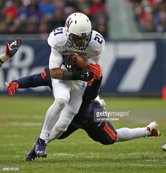 Justin Jackson of the Northwestern Wildcats breaks a tackle attrempt by TJ Neal of the Illinois Fighting Illini at Soldier Field on November 28 2015...