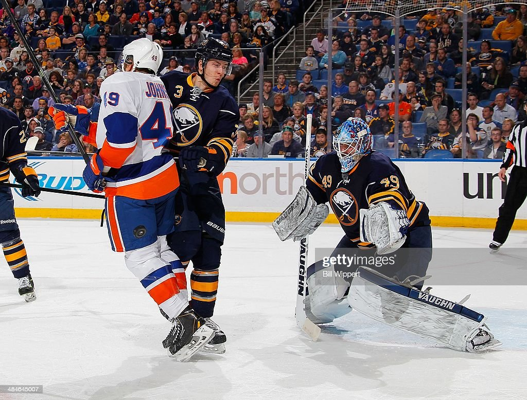 Justin Johnson #49 of the New York Islanders tries to deflect the puck while defended by Mark Pysyk #3 and Connor Knapp #49 of the Buffalo Sabres on April 13, 2014 at the First Niagara Center in Buffalo, New York.