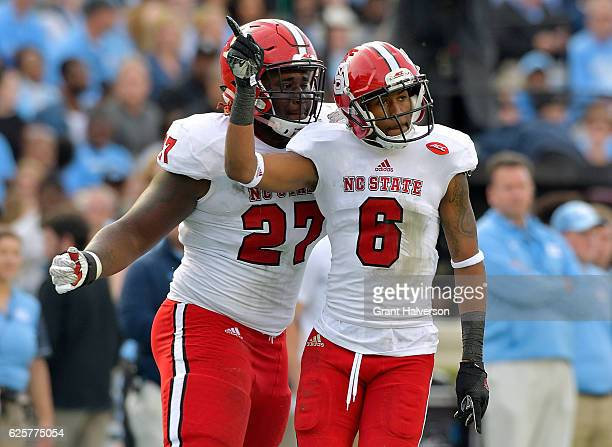 Justin Jones and Niles Clark of the North Carolina State Wolfpack react after making a defensive stop against the North Carolina Tar Heels during...