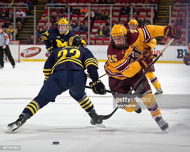 Justin Kloos f the Minnesota Golden Gophers slides the puck between the legs and skates around Andrew Sinelli of the Michigan Wolverines during the...