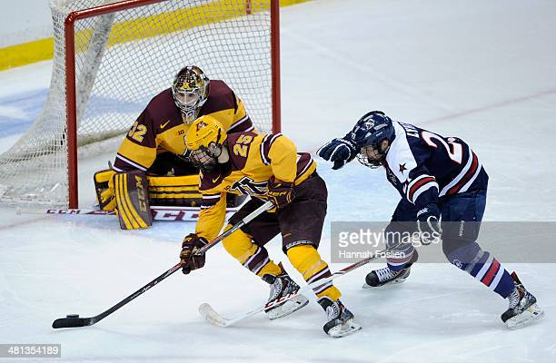 Justin Kloos of the Minnesota Golden Gophers controls the puck in front of teammate Adam Wilcox against Zac Lynch of the Robert Morris Colonials...