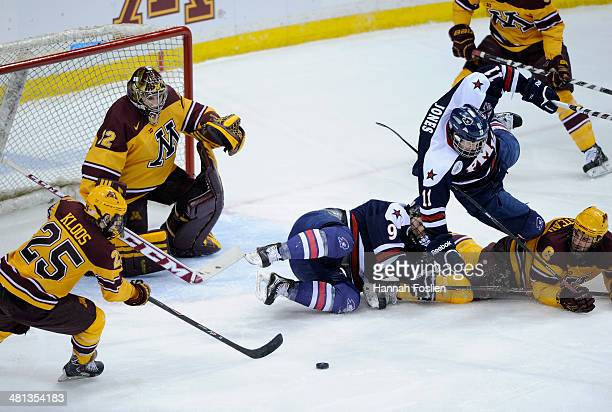 Justin Kloos of the Minnesota Golden Gophers takes the puck as Jeff Jones of the Robert Morris Colonials trips over teammate David Friedmann and Jake...