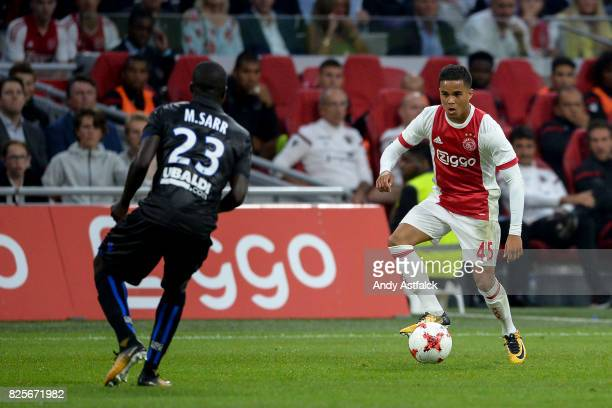 Justin Kluivert from AJAX is watched by Malang Sarr from OSC Nice during the UEFA Champions League Qualifying Third Round Second Leg match between...