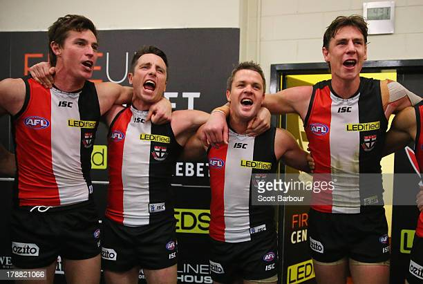 Justin Koschitzke Stephen Milne and Adam Schneider of the Saints sing the team song in the changing rooms after winning the round 23 AFL match...