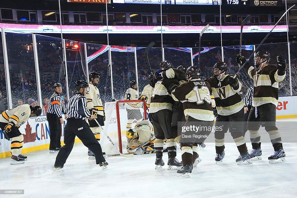 Justin Kovacs #17 of the Western Michigan Broncos is surrounded by teammates after he scored the game winning goal in O.T. on goaltender Pheonix Copley #31 of the Michigan Tech Huskies during the championship game of the Hockeytown Winter Festival Great Lakes Invitational - Day 2 played outdoors at Comerica Park on December 28, 2013 in Detroit, Michigan.