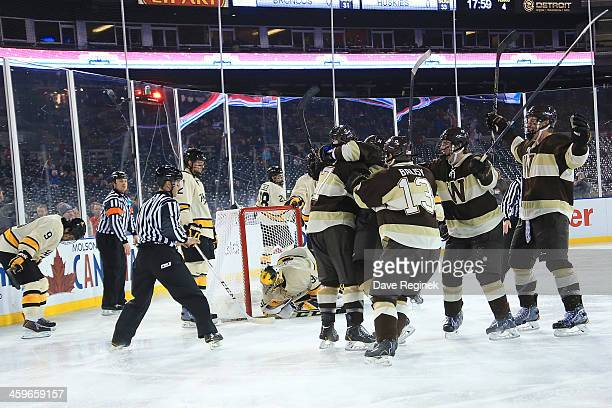Justin Kovacs of the Western Michigan Broncos is surrounded by teammates after he scored the game winning goal in OT on goaltender Pheonix Copley of...