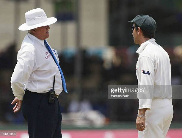 Justin Langer of Australia and umpire David Orchard discuss an incident that lead to the third umpire being called to investigate an appeal for hit...
