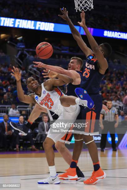 Justin Leon of the Florida Gators is blocked by Mamadi Diakite and Jack Salt of the Virginia Cavaliers in the first half during the second round of...