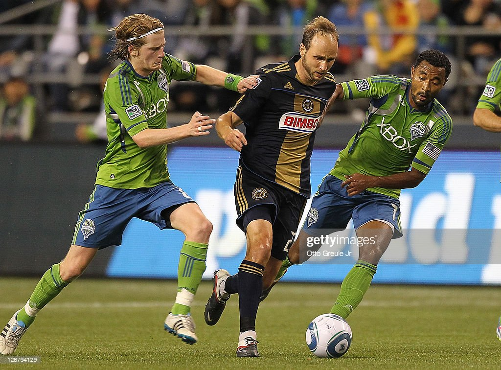 Justin Mapp of the Philadelphia Union battles Erik Friberg and James Riley of the Seattle Sounders FC at CenturyLink Field on October 8 2011 in...
