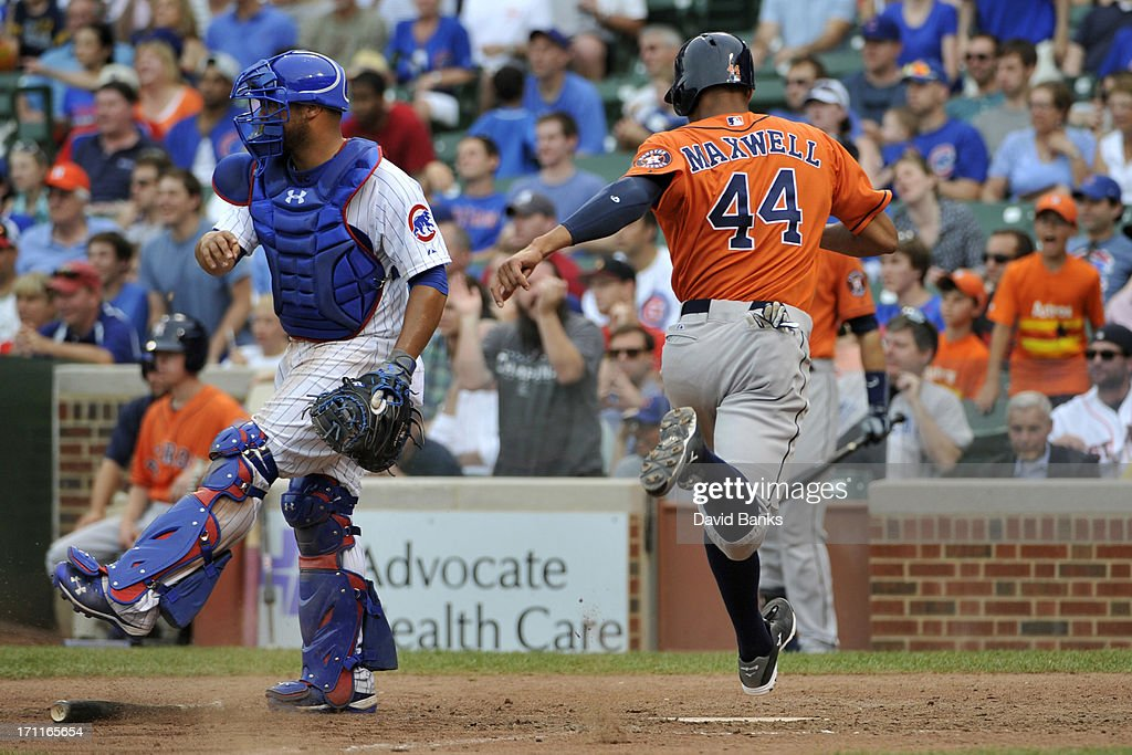 Justin Maxwell #44 of the Houston Astros scores the go-ahead run as Welington Castillo #53 of the Chicago Cubs looks on during the ninth inning on June 22, 2013 at Wrigley Field in Chicago, Illinois.