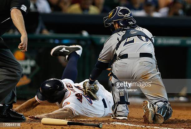 Justin Maxwell of the Houston Astros slides safe into home plate in the fifth inning under the tag of Jonathan Lucroy of the Milwaukee Brewers at...