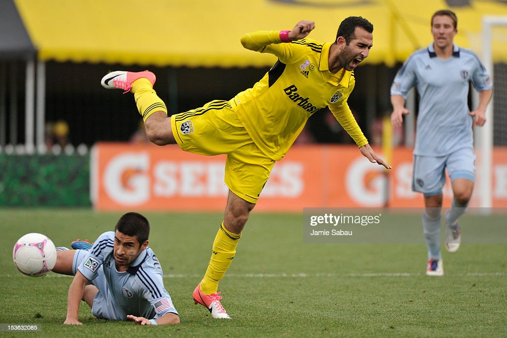 Justin Meram #9 of the Columbus Crew is tripped up by <a gi-track='captionPersonalityLinkClicked' href=/galleries/search?phrase=Paulo+Nagamura&family=editorial&specificpeople=577420 ng-click='$event.stopPropagation()'>Paulo Nagamura</a> #6 of Sporting Kansas City after Nagamura slid in to take the ball away on October 7, 2012 at Crew Stadium in Columbus, Ohio.