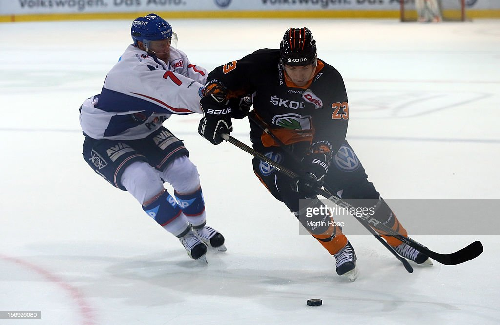 Justin Mercier (R) of Wolfsburg battles for the puck with Nikolai Goc (L) of Mannheim during the DEL match between Wolfsburg Grizzly Adams and Adler Mannheim at Volksbank BraWo EisArena on November 25, 2012 in Wolfsburg, Germany.