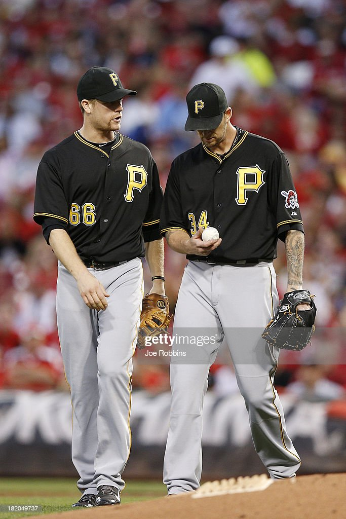 <a gi-track='captionPersonalityLinkClicked' href=/galleries/search?phrase=Justin+Morneau&family=editorial&specificpeople=211556 ng-click='$event.stopPropagation()'>Justin Morneau</a> #66 and <a gi-track='captionPersonalityLinkClicked' href=/galleries/search?phrase=A.J.+Burnett&family=editorial&specificpeople=213103 ng-click='$event.stopPropagation()'>A.J. Burnett</a> #34 of the Pittsburgh Pirates talk on the mound during the game against the Cincinnati Reds at Great American Ball Park on September 27, 2013 in Cincinnati, Ohio. The Pirates won 4-1.