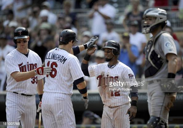 Justin Morneau and Alexi Casilla of the Minnesota Twins congratulate Josh Willingham on a two run home run as Jesus Montero of the Seattle Mariners...
