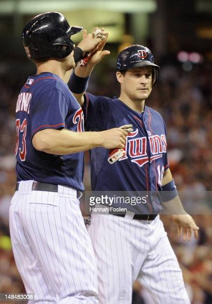 Justin Morneau and Josh Willingham of the Minnesota Twins celebrate scoring against the Baltimore Orioles during the fifth inning on July 17 2012 at...