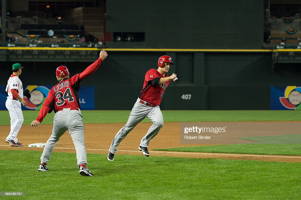 Justin Morneau #33 of Team Canada is waved home by third base coach Tim Leiper #34 in the top of the first inning of Pool D, Game 4 against Team Mexico in the first round of the 2013 World Baseball Classic at Chase Field on Saturday, March 9, 2013 in Phoenix, Arizona.