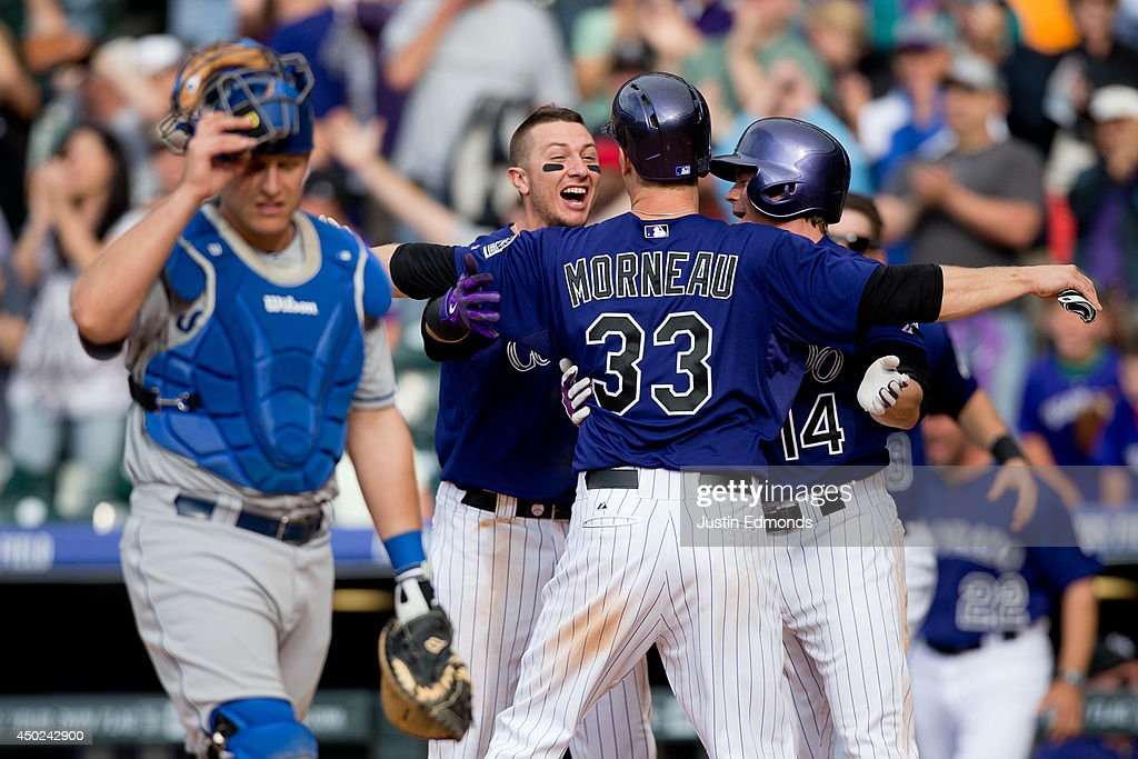 Justin Morneau #33 of the Colorado Rockies celebrates with Troy Tulowitzki #2 and Josh Rutledge #14 after scoring the winning run in the 10th inning on a triple by Brandon Barnes (not pictured) as catcher Tim Federowicz #26 of the Los Angeles Dodgers walks off the field at Coors Field on June 7, 2014 in Denver, Colorado. The Rockies defeated the Dodgers 5-4 in 10 innings to end their eight game losing streak.