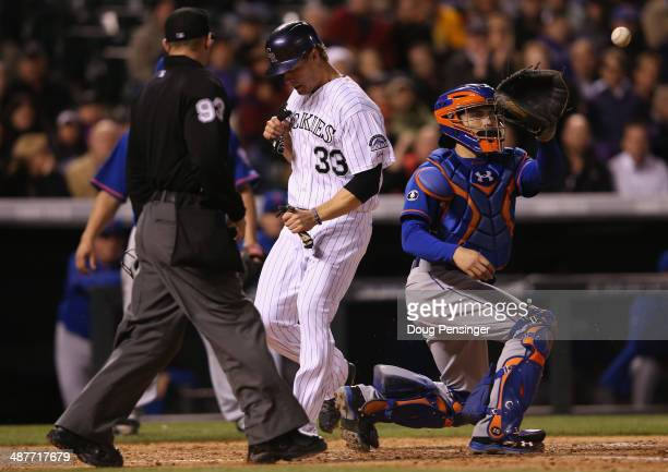 Justin Morneau of the Colorado Rockies scores on a triple by Corey Dickerson of the Colorado Rockies as catcher Travis d'Arnaud of the New York Mets...