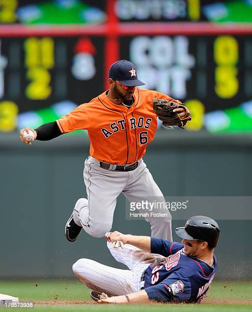 Justin Morneau of the Minnesota Twins breaks up a double play by Jonathan Villar of the Houston Astros as he is out at second base during the fourth...