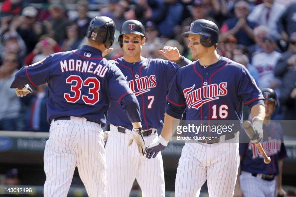 Justin Morneau of the Minnesota Twins celebrates his home run against the Los Angeles Angels with Joe Mauer and Josh Willingham on April 12 2012 at...