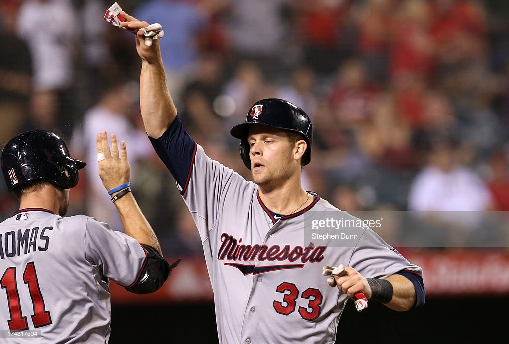 Justin Morneau #33 of the Minnesota Twins celebrates with <a gi-track='captionPersonalityLinkClicked' href=/galleries/search?phrase=Clete+Thomas&family=editorial&specificpeople=4952485 ng-click='$event.stopPropagation()'>Clete Thomas</a> #11 after scoring a run to put the Twins ahead 3-2 in the eighth inning against the Los Angeles Angels of Anaheim at Angel Stadium of Anaheim on July 23, 2013 in Anaheim, California.