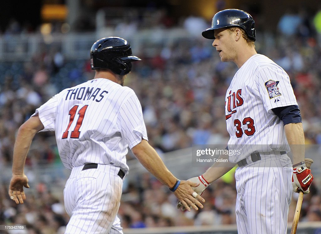 Justin Morneau #33 of the Minnesota Twins congratulates teammate Clete Thomas #11 on scoring a run against the Houston Astros during the third inning of the game on August 2, 2013 at Target Field in Minneapolis, Minnesota.