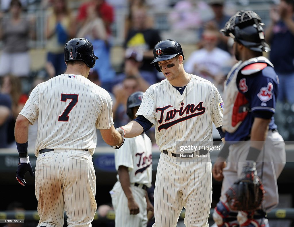 <a gi-track='captionPersonalityLinkClicked' href=/galleries/search?phrase=Justin+Morneau&family=editorial&specificpeople=211556 ng-click='$event.stopPropagation()'>Justin Morneau</a> #33 of the Minnesota Twins congratulates teammate <a gi-track='captionPersonalityLinkClicked' href=/galleries/search?phrase=Joe+Mauer&family=editorial&specificpeople=214614 ng-click='$event.stopPropagation()'>Joe Mauer</a> #7 on a solo home run as Carlos Santana #41 of the Cleveland Indians looks on during the tenth inning of the game on August 14, 2013 at Target Field in Minneapolis, Minnesota. The Indians defeated the Twins 9-8 in twelve innings.