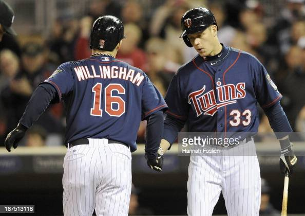 Justin Morneau of the Minnesota Twins congratulates teammate Josh Willingham on a solo home run against the Texas Rangers during the seventh inning...
