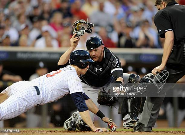 Justin Morneau of the Minnesota Twins dives for home plate as Tyler Flowers of the Chicago White Sox reaches to apply a tag and umpire Jordan Baker...