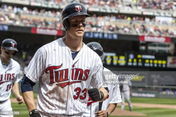 Justin Morneau of the Minnesota Twins heads to the dugout after a home run in the sixth inning as Josh Willingham follows in game against the Texas...