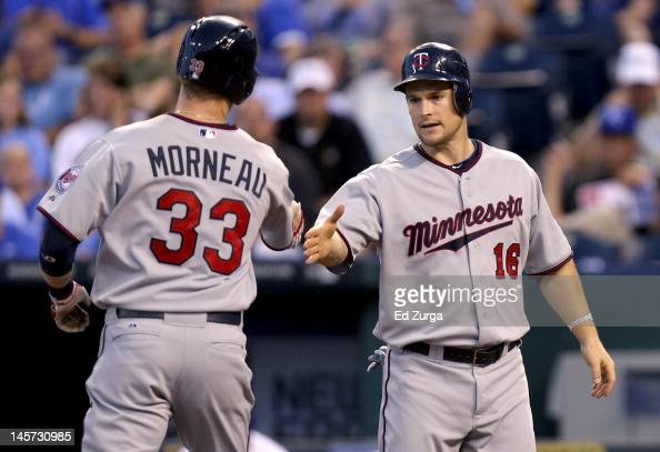 Justin Morneau of the Minnesota Twins is congratulated by Josh Willingham after hitting a tworun home run against the Kansas City Royals in the fifth...