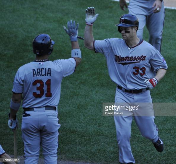 Justin Morneau of the Minnesota Twins is greeted by Oswaldo Arcia after hitting a threerun homer against the Chicago White Sox during the third...
