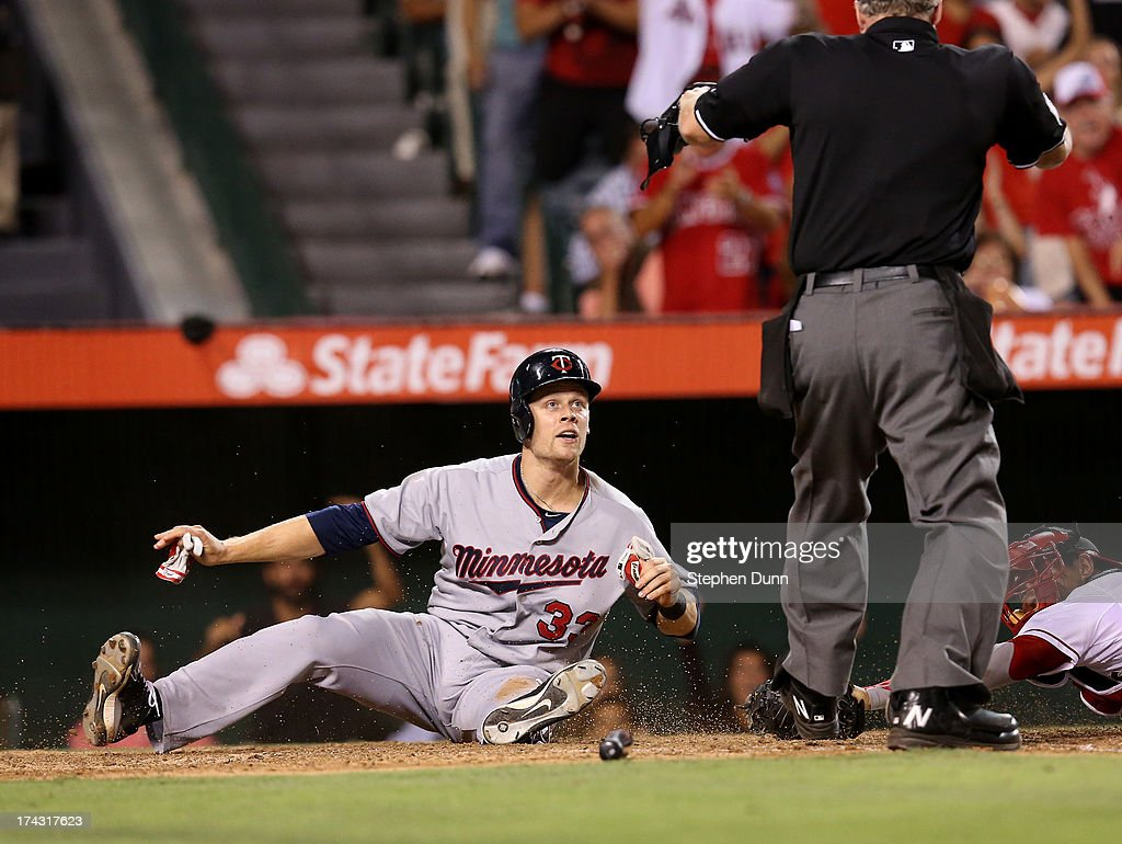Justin Morneau #33 of the Minnesota Twins looks to home plate umpire Ted Barrett for the safe call after sliding past catcher Hank Conger #16 of the Los Angeles Angels of Anaheim to score a run putting the Twins ahead 3-2 in the eighth inning at Angel Stadium of Anaheim on July 23, 2013 in Anaheim, California.