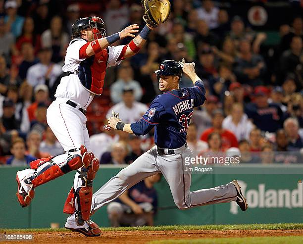 Justin Morneau of the Minnesota Twins scores as Jarrod Saltalamacchia of the Boston Red Sox leaps for a high throw in the 8th inning at Fenway Park...