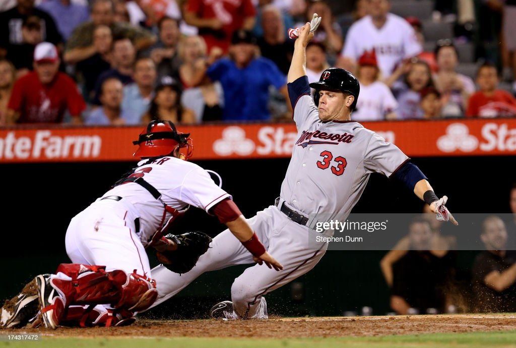 <a gi-track='captionPersonalityLinkClicked' href=/galleries/search?phrase=Justin+Morneau&family=editorial&specificpeople=211556 ng-click='$event.stopPropagation()'>Justin Morneau</a> #33 of the Minnesota Twins slides past catcher <a gi-track='captionPersonalityLinkClicked' href=/galleries/search?phrase=Hank+Conger&family=editorial&specificpeople=713039 ng-click='$event.stopPropagation()'>Hank Conger</a> #16 of the Los Angeles Angels of Anaheim to score a run putting the Twins ahead 3-2 in the eighth inning at Angel Stadium of Anaheim on July 23, 2013 in Anaheim, California.