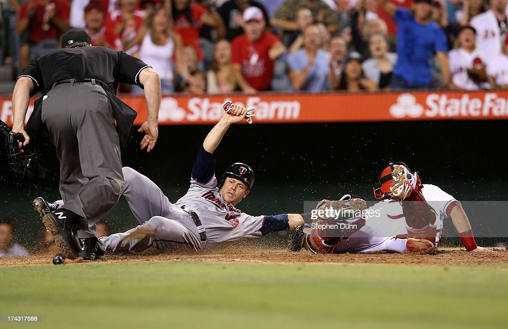 Justin Morneau #33 of the Minnesota Twins slides past catcher <a gi-track='captionPersonalityLinkClicked' href=/galleries/search?phrase=Hank+Conger&family=editorial&specificpeople=713039 ng-click='$event.stopPropagation()'>Hank Conger</a> #16 of the Los Angeles Angels of Anaheim to score a run putting the Twins ahead 3-2 in the eighth inning at Angel Stadium of Anaheim on July 23, 2013 in Anaheim, California.