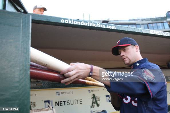 Justin Morneau of the Minnesota Twins stows his bats in the dugout before the game against the Oakland Athletics at the OaklandAlameda County...