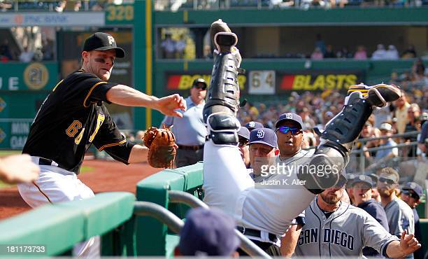 Justin Morneau of the Pittsburgh Pirates attempts to reach for Tony Sanchez of the Pittsburgh Pirates who tumbles over the railing after catching a...