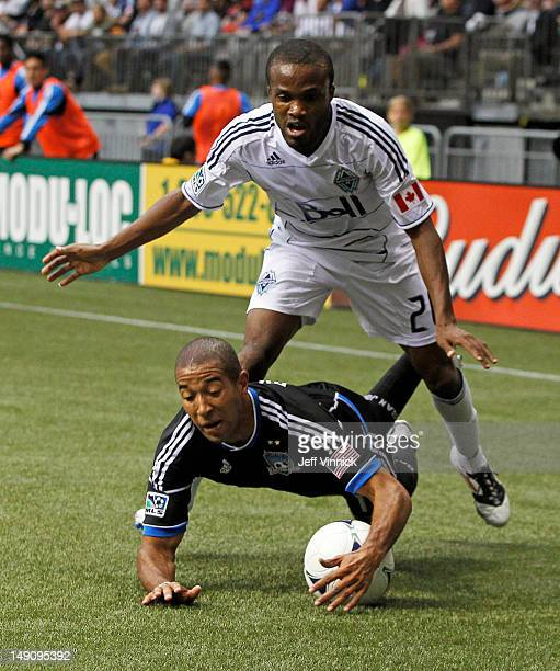 Justin Morrow of the San Jose Earthquakes is knocked to the turf by Dane Richards of the Vancouver Whitecaps FC as they battle for the ball during...