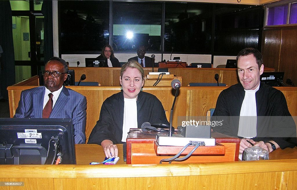 Justin Mugenzi (L) is pictured next to his lawyers at the International Criminal Tribunal for Rwanda (ICTR) in Arusha on February 4, 2013. An UN appeal court has overturned genocide convictions of two Rwandan ex-ministers who were jailed for 30 years in 2011, and ordered their immediate release. Appeal judge Theodor Meron overturned convictions for complicity to commit genocide and incitement to commit genocide against Justin Mugenzi, who was trade minister during the 1994 genocide, and Prosper Mugiraneza, former minister in charge of civil servants. AFP PHOTO