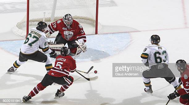 Justin Nichols of the Guelph Storm stops an attempt by Kole Sherwood of the London Knights during an OHL game at Budweiser Gardens on December 18...