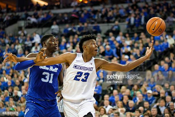 Justin Patton of the Creighton Bluejays reaches for the ball while being guarded by Angel Delgado of the Seton Hall Pirates during their game at the...