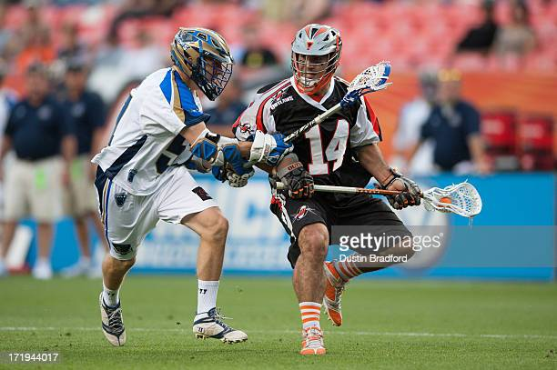 Justin Pennington of the Denver Outlaws drives and is covered by Peet Poillon of the Charlotte Hounds during a Major League Lacrosse game at Sports...