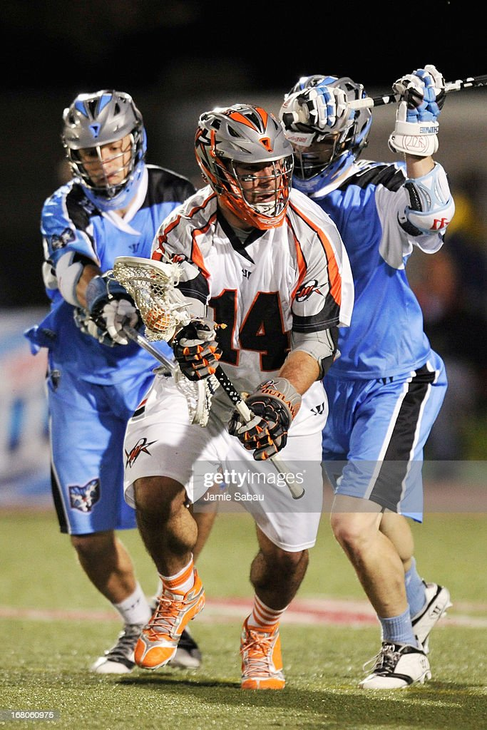 Justin Pennington #14 of the Denver Outlaws eludes the defensive pressure of Kyle Hartzell #81 of the Ohio Machine and Brett Garber #3 of the Ohio Machine in the second half on May 4, 2013 at Selby Stadium in Delaware, Ohio. Denver defeated Ohio 13-8.